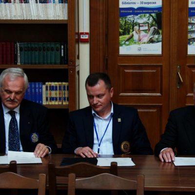 3 prezydentów podpisujący akt przekazania skanera dla Biblioteki